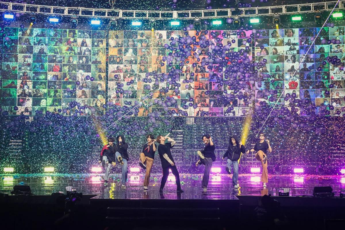 Imagem do BTS em uma performance transmitida online. Os membros estão num palco se apresentando e atrás deles existe um painel mostrando imagens de centenas de pessoas que estavam assistindo a apresentação. O palco é coberto de confetes brilhantes e bexigas, provavelmente celebrando o fim do show.