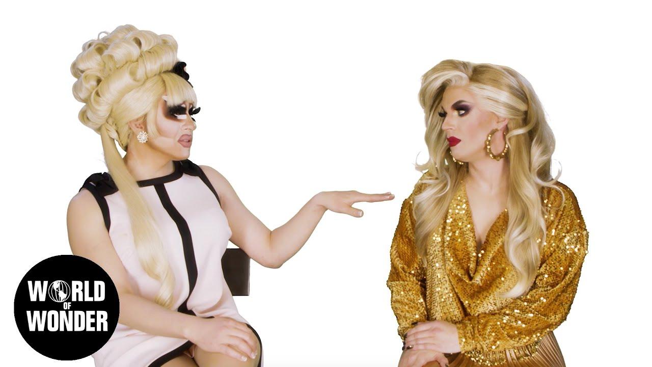 Cena do programa UNHhhh. À direita vemos Trixie Mattel, uma drag queen branca e de peruca loira. Ela veste um vestido branco com detalhes em preto na gola e uma linha no meio da roupa. Ela está quase tocando Katya, uma drag queen branca e de peruca loira, que usa um macacão dourado. Ao fundo, um fundo branco e no canto inferior esquerdo, está um logo preto e redondo, com as palavras World of Wonder escritas em branco. O primeiro O de World é o desenho do globo terrestre.