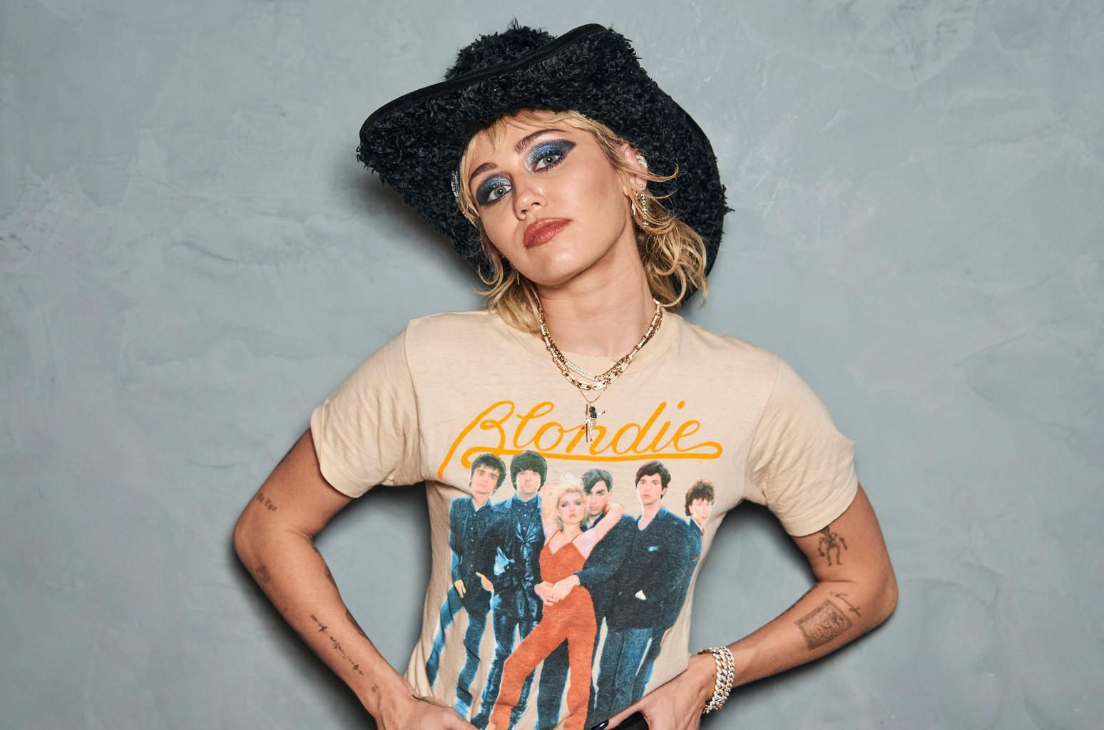 Fotografia de Miley Cyrus. A artista está posicionada ao centro, da cintura pra cima, de frente para a câmera. Seu rosto está levemente inclinado para o lado esquerdo da imagem e suas mãos estão enganchadas na cintura. Seus cabelos loiros são curtos, na altura do ombro, e estão bagunçados, meio ondulados. Ela também usa uma franja na altura das sobrancelhas e um chapéu country preto de pelinhos. Miley usa uma maquiagem azul metálica e cinza escura e um batom marrom médio. Ela veste uma camiseta da banda Blondie, que mostra os membros e o logo da banda em cima, numa fonte cursiva e em amarelo. Ela também usa colares dourados finos e uma pulseira de corrente prateada na mão direita.