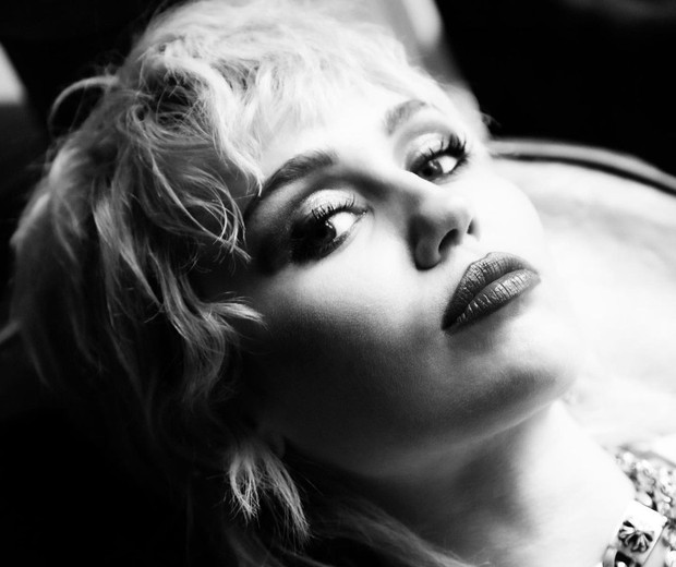 Fotografia em preto e branco da artista Miley Cyrus. Ela está de lado e a imagem capta apenas seu rosto, que está inclinado para o lado direto. Miley encara a câmera com uma expressão séria mas serena. Seus cabelos loiros são curtos, na altura no queixo, e ela também usa uma franja um pouco acima da sobrancelha. Miley usa maquiagem nos olhos e um batom escuro. A artista está deitada e apoia a cabeça nas costas de um divã.