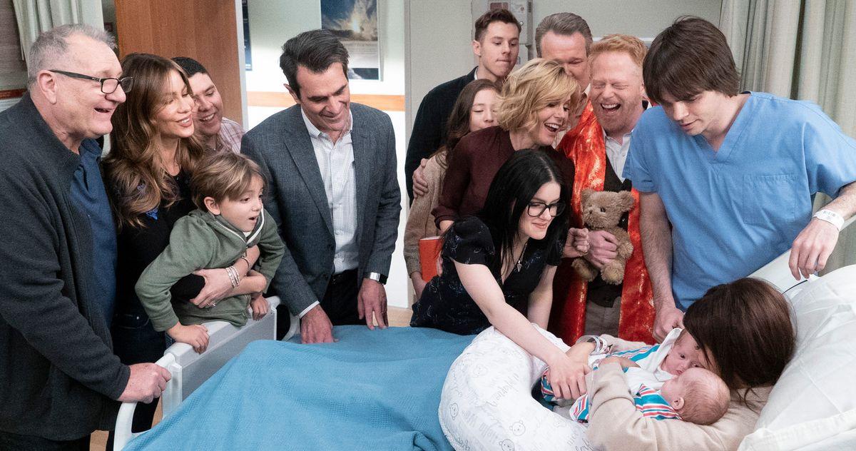 A imagem é de uma cena da série Modern Family. Nela, podemos ver toda a família Dunphy-Delgado-Tucker-Pritchett sorrindo reunida em uma sala de hospital, em volta de uma cama, onde a personagem Haley está deitada segurando seus filhos gêmeos. Haley, interpretada por Sarah Hyland, é uma jovem branca de cabelos castanhos compridos. Em volta da cama, da esquerda para a direita, estão: Jay, interpretado por Ed O'Neil, que é um homem branco de aparentemente 60 anos, com cabelos grisalhos, óculos e que está vestindo uma blusa preta de mangas compridas; Glória, interpretada por Sofia Vergara, que é uma mulher de traços latinos, cabelos castanhos claros compridos, está vestindo uma blusa preta e abraçando seu filho Joe por trás; Joe, interpretado por Jeremy Maguire, é um menino branco de cabelos castanhos claros curtos, e que está vestindo uma blusa verde de mangas compridas; Manny, interpretado por Rico Rodriguez, é um jovem de traços latinos, cabelo castanho escuro ralo; Phil, interpretado por Ty Burrell, que é um homem branco de cabelos pretos curtos, e veste uma camisa branca com um terno cinza; Alex, interpretada por Ariel Winter, que é uma mulher branca de cabelos pretos compridos, e veste uma blusa preta, ela está fazendo carinho nos gêmeos; Claire, interpretada por Julie Bowen, que é uma mulher branca de cabelos loiros curtos, ela veste uma blusa de mangas compridas na cor vinho e está atrás de Alex; Lily, interpretada por Aubrey Anderson-Emmons, que é uma adolescente de traços asiáticos, ela está atrás de Claire; Luke, interpretado por Nolan Goud, que é um jovem branco de cabelos castanhos claros curtos, ele veste uma blusa preta de mangas compridas e está atrás de Lily; ao lado de Lily, está Cam, interpretado por Eric Stonestreet, que é um homem branco de cabelos grisalhos curtos; ao lado de Claire, está Mitchell, interpretado por Jesse Tyler Ferguson, que é um homem branco de cabelos ruivos curtos, ele veste uma blusa laranja e carrega um ursinho nas mãos; e Dyla