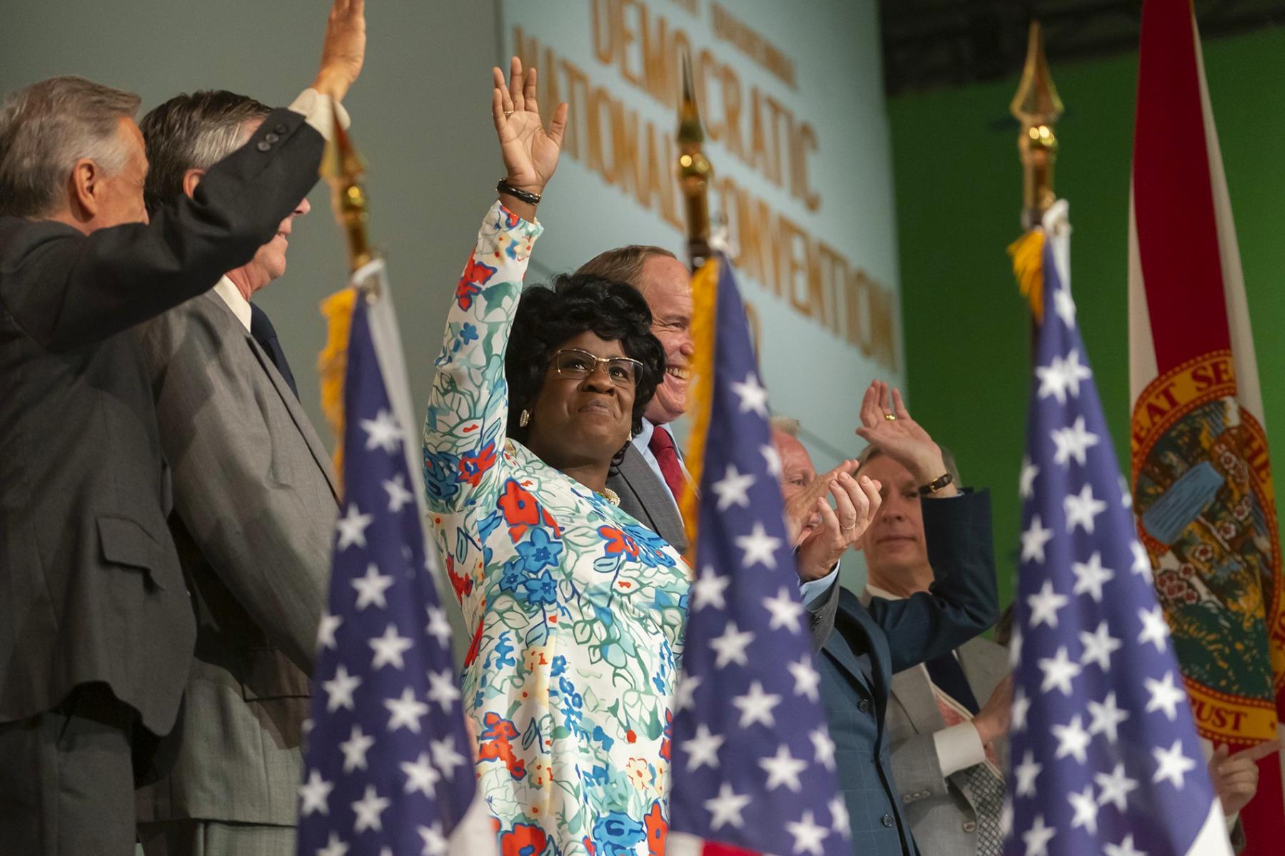 Cena da minissérie Mrs. America. Ao centro da imagem está a atriz Uzo Aduba interpretando a deputada Shirley Chisholm. Ela tem a pele negra, os cabelos pretos curtos, na altura da orelha e ondulados. A personagem também usa um vestido florido de fundo branco, com flores azuis, laranjas e vermelhas. Ela usa um óculos médio e quadrado dourado, e está de pé em um palco, mas nós a vemos de baixo, do quadril para cima. Ela está olhando para a frente, sorrindo levemente e acenando, e ao seu redor, estão cinco homens brancos, também acenando e vestindo ternos. No primeiro plano da imagem, na frente dos personagens mas sem foco, existem três bandeiras dos Estados Unidos.