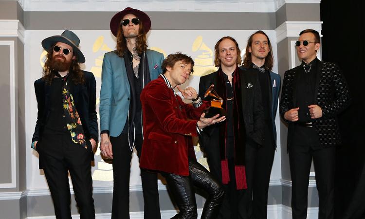 6 homens posando para foto no Grammy de 2017. No meio, um deles segura o prêmio e faz uma pose meio torta para a câmera. Todos os homens são brancos, 4 deles tem cabelos compridos, 3 usam óculos escuros e 1 deles tem barba