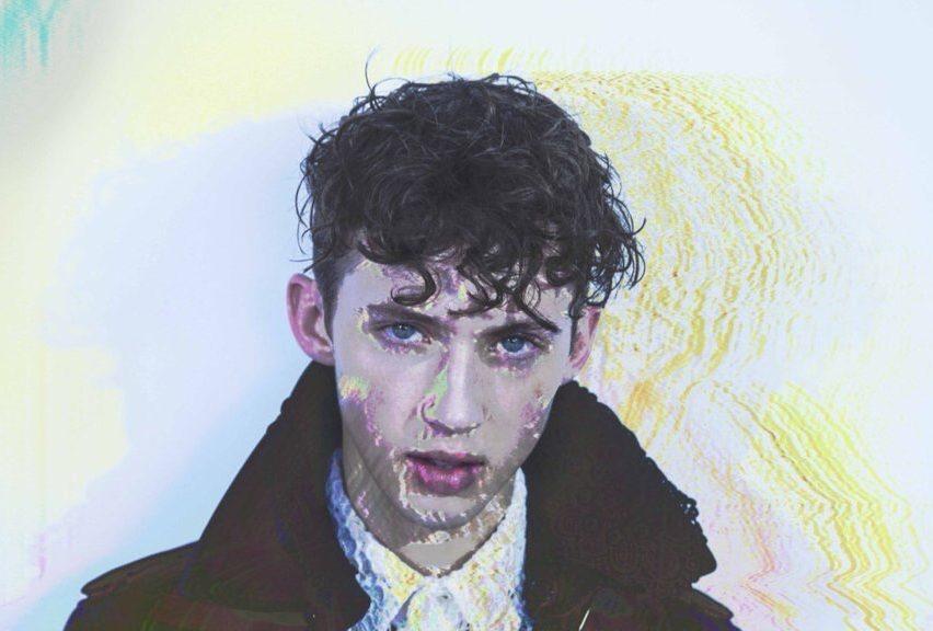A imagem mostra Troye Sivan se espreguiçando, olhando diretamente para a câmera, de frente. Ele usa um casaco preto e uma camisa branca por baixo. Foi adicionado um efeito de glitch na imagem.