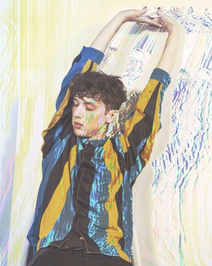 A imagem mostra Troye Sivan se espreguiçando, de olhos fechados. Ele usa uma camiseta com listras verticais azuis, amarelas e pretas. Foi adicionado um efeito de glitch na imagem.