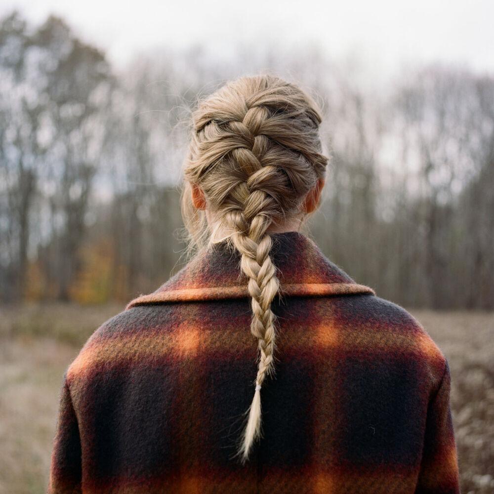 Capa do álbum 'evermore' de Taylor Swift. A imagem apresenta Taylor de costas, fotografada da metade das costas para cima. Ela tem a pele branca e seus cabelos loiros, na altura do meio das costas, estão presos numa trança embutida. Ela usa uma blusa de flanela com uma estampa xadrez grande, de fundo azul bem escuro e os quadrados são laranja, amarelo e bege. Ela está de frente para um um gramado e logo à frente uma parede de árvores longas, de troncos finos e folhagens abertas. A paisagem ao fundo da imagem para onde Taylor olha está desfocada.