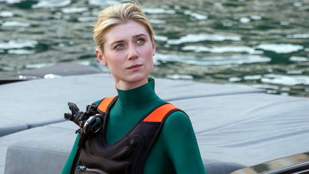 Elizabeth Debicki, uma mulher loira e branca, está usando um traje de mergulho verde e uma colete preto com detalhes laranjas no ombro. Ela está numa lancha, vemos o mar ao fundo. Seu cabelo loiro está preso num coque e ela olha para a esquerda, num lugar que a câmera não vê.