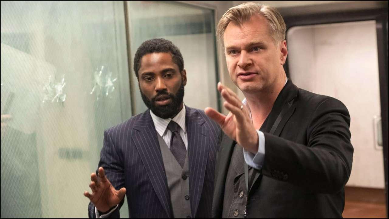 Nolan e John David Washington estão na foto. Washington é negro e tem uma barba feita, ele usa terno preto e gesticula com as mãos, olhando para baixo. Nolan é branco, também gesticula com as mãos, mas ele olha para frente