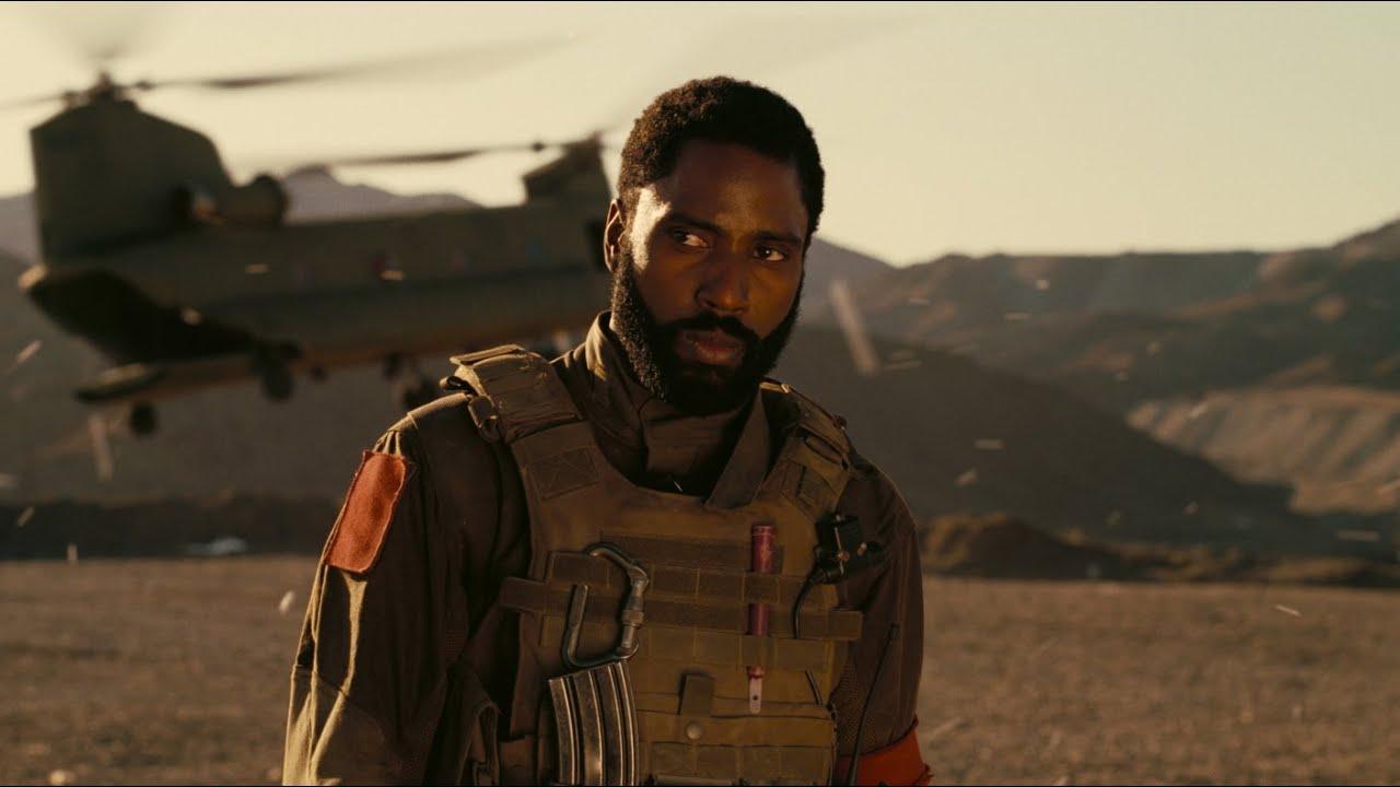 John David Washington está num deserto montanhoso, atrás dele, desfocado, está uma avião. Ele é um homem negro de 30 anos, com barba feita e usa um colete militar escuro e sujo de areia e terra.