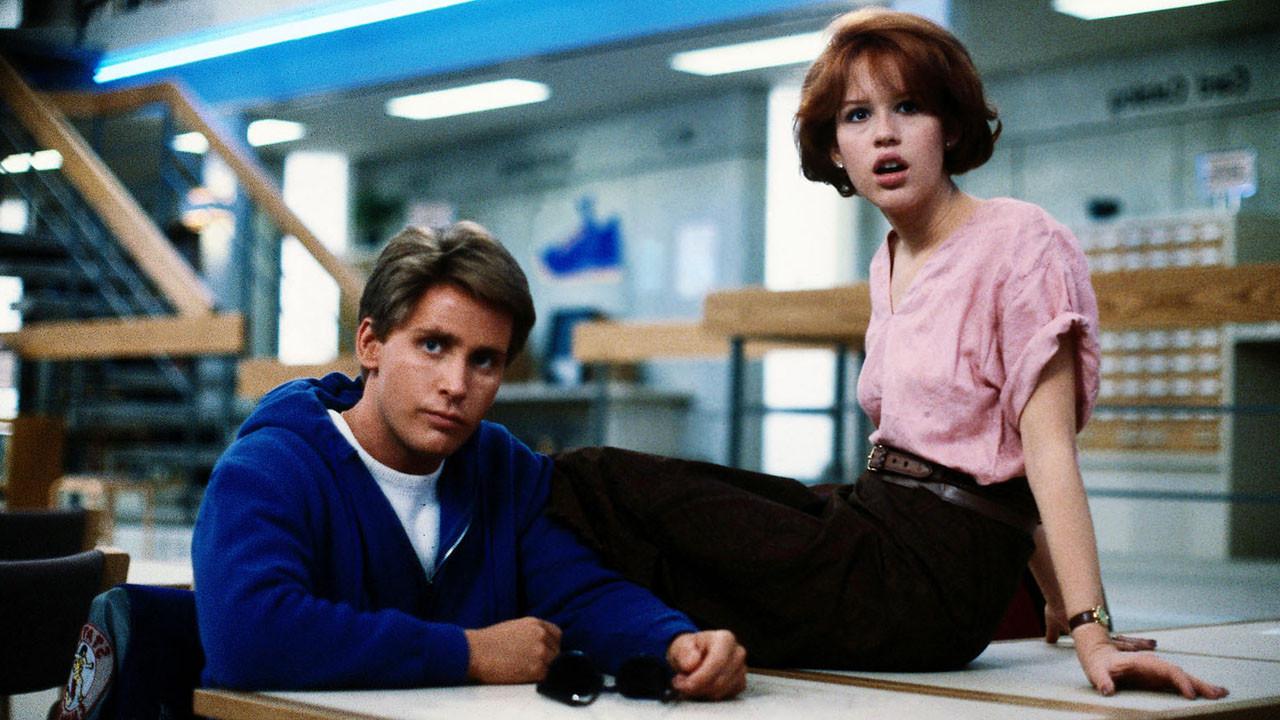 A imagem é de uma das cenas do filme. Nela, podemos ver os personagens Andrew e Claire na biblioteca. Andrew está sentado em uma cadeira, com os braços apoiados em cima da mesa. Enquanto Claire está sentada em cima da mesa, com os braços apoiados para trás, ela está boquiaberta.