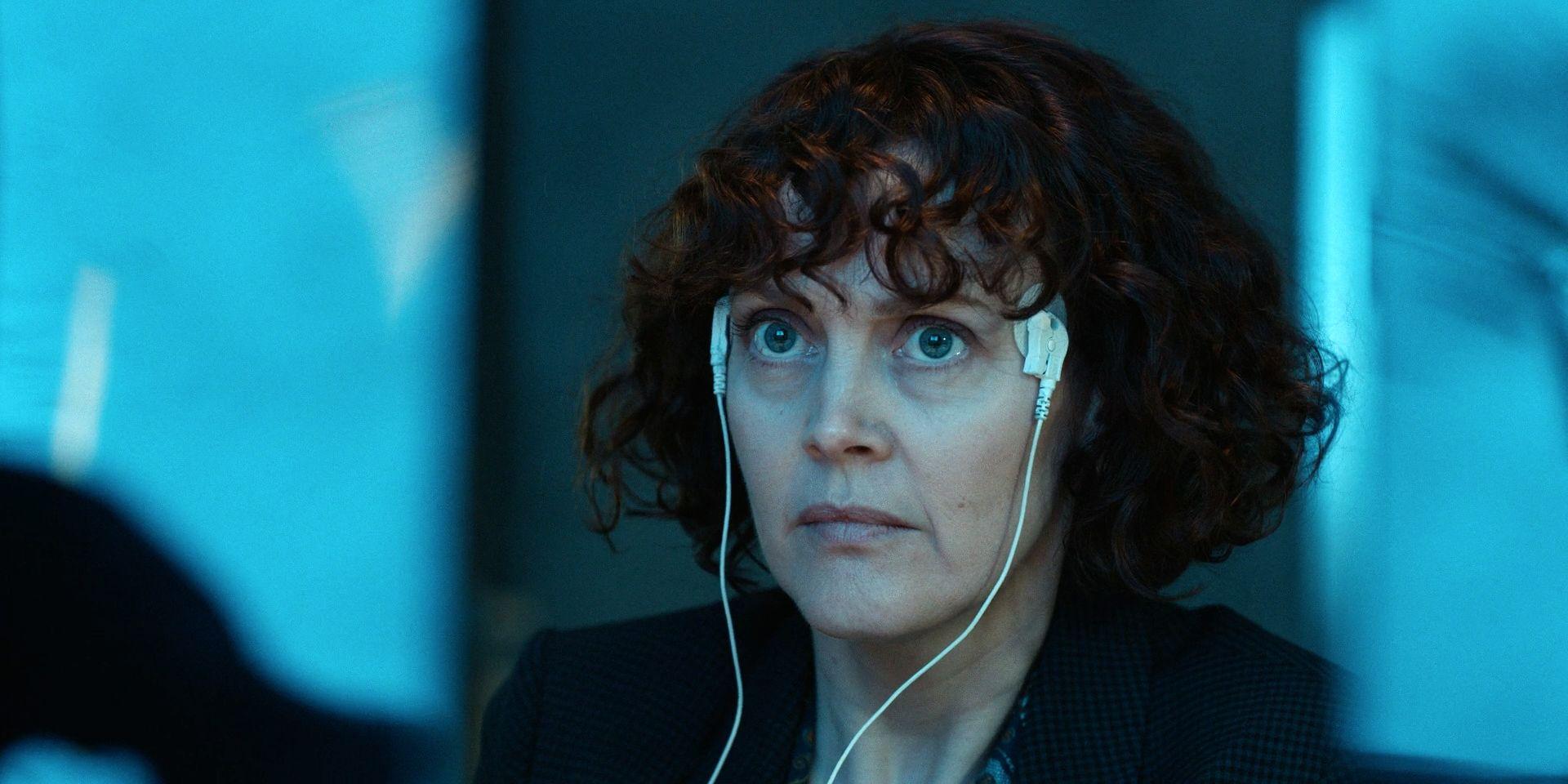 A imagem mostra Mary Malone no que parece ser um laboratório. Ela usa dois conectores em suas têmporas, e olha preocupada para cima.