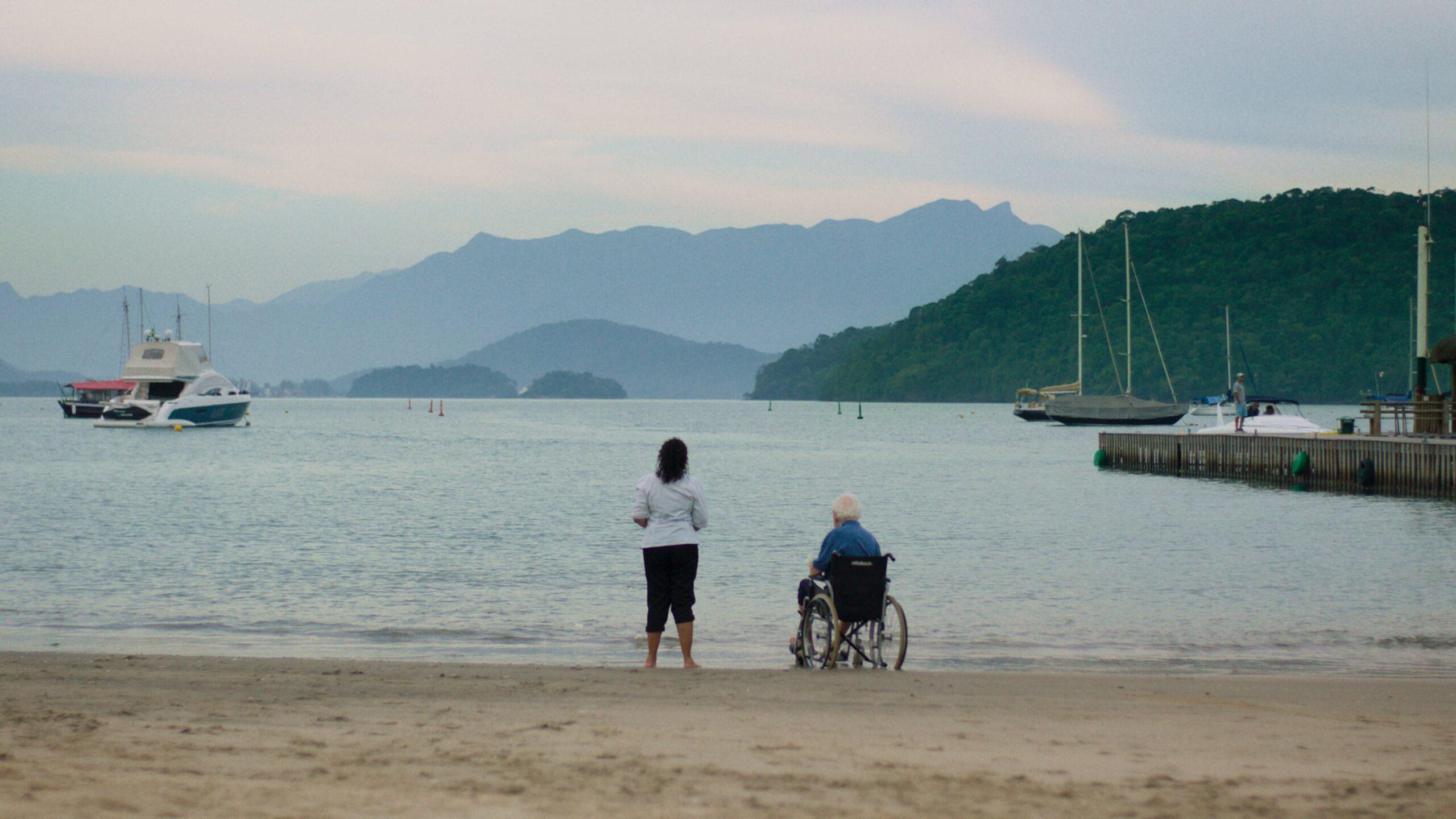 A imagem é de uma das cenas do filme. Nela, Madá e Seu Lira estão em uma praia, de frente para o mar e de costas para a imagem. Seu Lira está em uma cadeira de rodas e Madá está de pé, ao seu lado. No mar, é possível ver barcos e várias ilhas ao fundo.