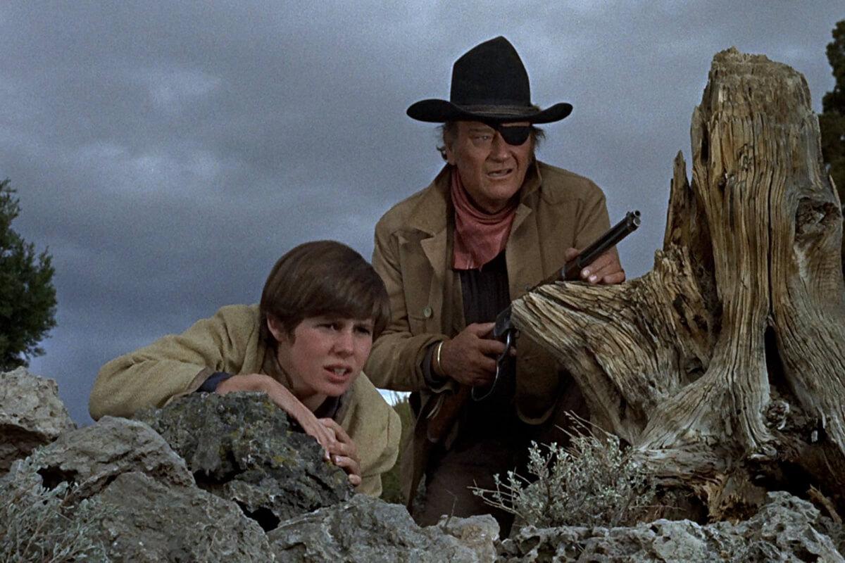 Cena do filme Bravura Indômita de 1969. A imagem mostra um garotinho e um homem se escondendo atrás de uma rocha. O homem usa tapa-olho e chapéu, e tem uma arma na mão.
