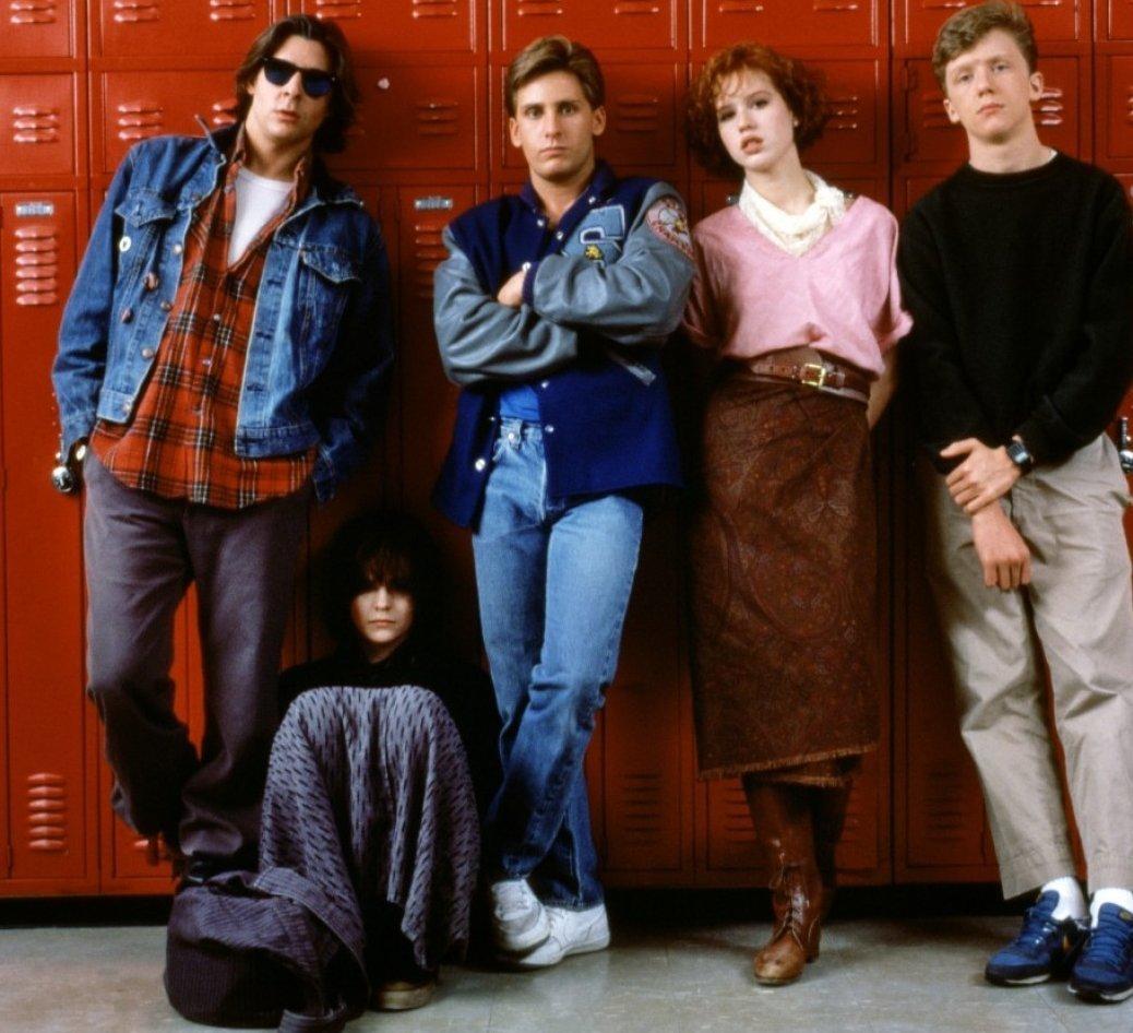 A imagem é uma fotografia dos personagens do filme, em frente à um armário escolar vermelho. Da esquerda para a direita estão: John, Allison, Andrew, Claire e Brian. John é um homem branco de cabelos castanhos lisos um pouco acima do ombro, ele usa um óculos escuro, jaqueta jeans, uma camisa xadrez vermelha e uma calça preta. John está encostado no armário, com o joelho direito dobrado. Allison é uma mulher branca, de cabelos castanhos curtos e franja, ela veste uma blusa preta de mangas compridas e uma saia cinza. Allison está sentada no chão, de joelhos dobrados em frente ao peito. Andrew é um homem branco de cabelos loiros curtos, ele veste um casaco azul estilo college, uma camiseta azul clara, uma calça jeans e tênis branco. Andrew está encostado no armário, com as pernas e braços cruzados. Claire é uma mulher banca, de cabelos ruivos acima dos ombros, ela veste uma blusa rosa, uma saia marrom e botas marrons. Claire está encostada no armário, com os braços cruzados para trás e as pernas também cruzadas. Brian é um homem branco com cabelos loiros curtos, ele veste uma blusa verde escura de mangas compridas, calças bege e um par de tênis azuis. Brian está encostado no armário, com a mão esquerda segurando seu pulso direito.