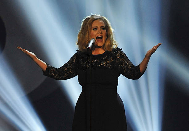 A imagem da cantora Adele mostra ela com um vestido tubinho preto com mangas três quartos. Ela tem os cabelos loiros soltos e volumosos, tem os dois braços abertos, assim como a boca. Em sua frente há um microfone e ao fundo há luzes azuis de show.