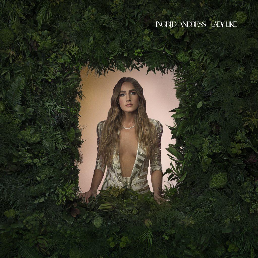 Capa do álbum Lady Like. A imagem mostra Ingrid Andress com um blazer de listras brancas e douradas abertas. Ela usa um colar de pérolas e tem os cabelos loiros, ondulados e soltos. Ela está em uma espécie de janela e em volta há diversas plantas, todas verdes.