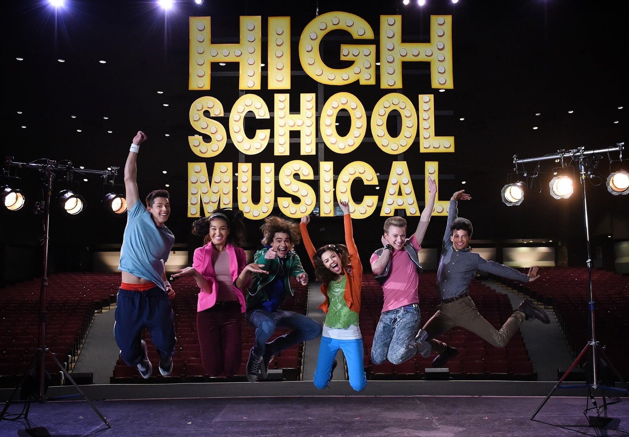 Cena da série High School Musical: The Musical: The Series. Vemos 6 alunos pulando no palco do teatro, atrás deles está um letreiro amarelo com as palavras High School Musical. Ao redor dos 6, vemos holofotes acesos. Na extrema esquerda, vemos E.J. Um adolescente branco e alto. Ele está pulando com a mão direita pro alto, no mesmo braço onde usa uma munhequeira branca. Ele usa blusa azul e calça jeans. Ao lado dele está Gina, mulher negra de blusa rosa. Ao lado dela está Ricky, sorrindo e apontando pra frente enquanto pula. Ele usa jaqueta verde, calça jeans e uma peruca castanha. Ao seu lado está Nini, garota de ascendência asiática, pele clara e cabelos escuros. Ela pula com os dois braços pra cima e com a boca aberta. Ela usa calça azul, camiseta verde e uma blusa laranja de manga longa por cima. Ao seu lado, está Seb. Um jovem branco e loiro, com a mão direita no queixo e a esquerda para cima. Ele usa calça jeans clara e uma camiseta rosa com bolero cinza. Na ponta direita está o intérprete de Ryan, pulando com os braços para os lados, de calça caqui e blusa azul de botão. Ele usa uma boina, tem pele clara e sorri.