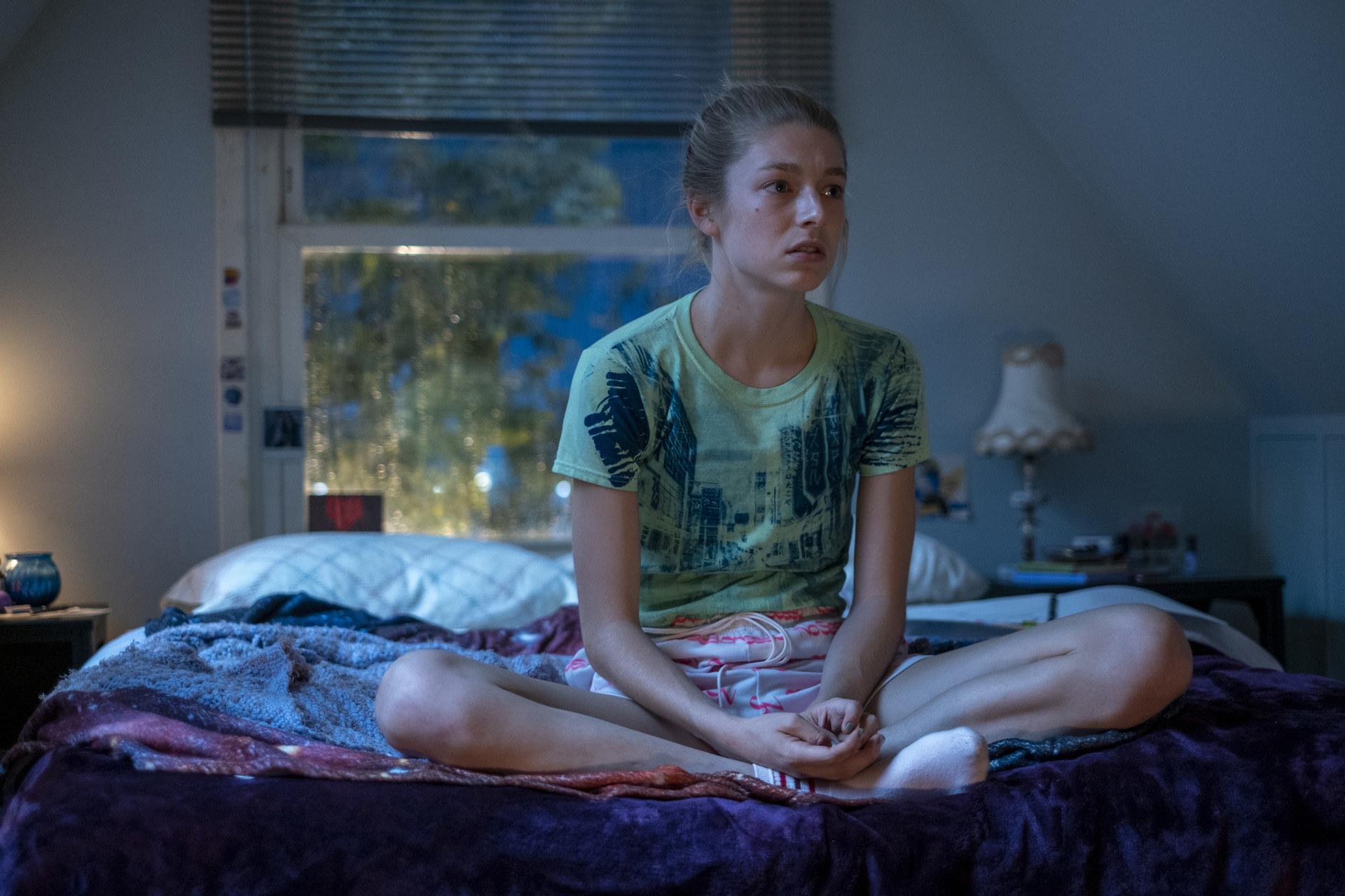 Cena do episódio Part 2: Jules de Euphoria. Jules está sentada na cama com as pernas em posição de índio. Jules é uma adolescente de pele clara e cabelos loiros quase brancos. Ela os tem preso num coque, e usa uma camiseta verde com detalhes azuis que formam uma rua na estampa. Ela veste shorts curtos e claros, e tem as mãos em cima dos pés. Ao fundo, vemos um abajur branco, um travesseiro branco e a janela do quarto, está de noite.
