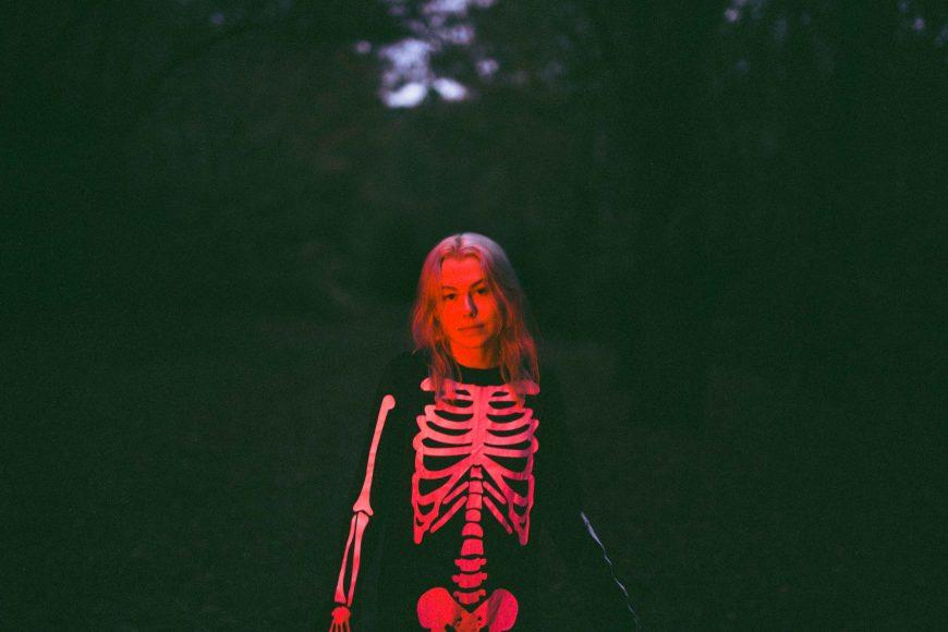 Imagem de Phoebe Bridgers da cintura para cima. Ela usa um macacão preto com desenho de esqueleto e tem os cabelos loiros soltos. Ao fundo há algumas árvores. Uma luz vermelha ilumina o rosto da cantora.