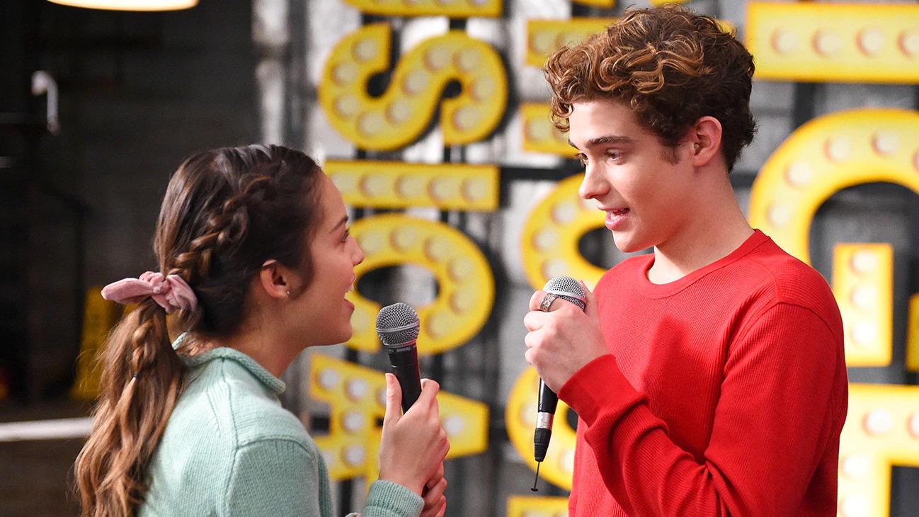 Cena da série High School Musical: The Musical: The Series. Ricky e Nini cantam um para o outro. Ricky é um jovem branco, de pele clara e cabelos castanhos encaracolados. Nini é uma jovem de ascendência asiática, de pele clara e cabelos pretos. Eles seguram microfones, ele usa um moletom vermelho e ela está de jaqueta jeans e xuxinha rosa no rabo de cavalo.