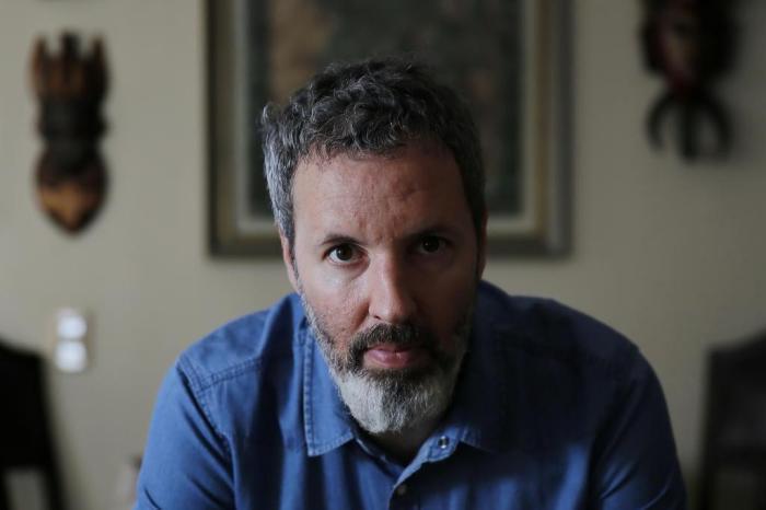 A imagem contém a foto do escritor Michel Laub, ele tem cabelos curtos escuros e grisalhos, barba grisalha e bigode, pele branca e veste camisa azul. Ele encara diretamente a camera e ao fundo existe um quadro desfocado.
