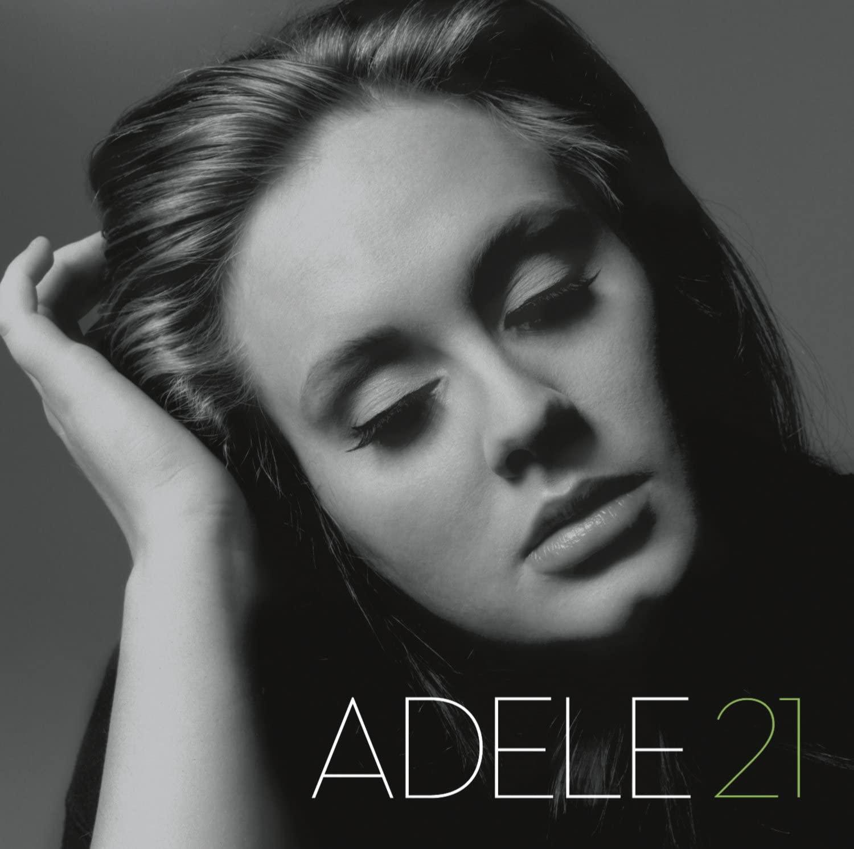 Capa do álbum 21 da Adele. Ele mostra o rosto da cantora de olhos fechados. Ela tem os cabelos soltos e penteados para trás, pele clara e a mão apoiando a cabeça. A imagem é em preto e branco com o número 21 em verde.