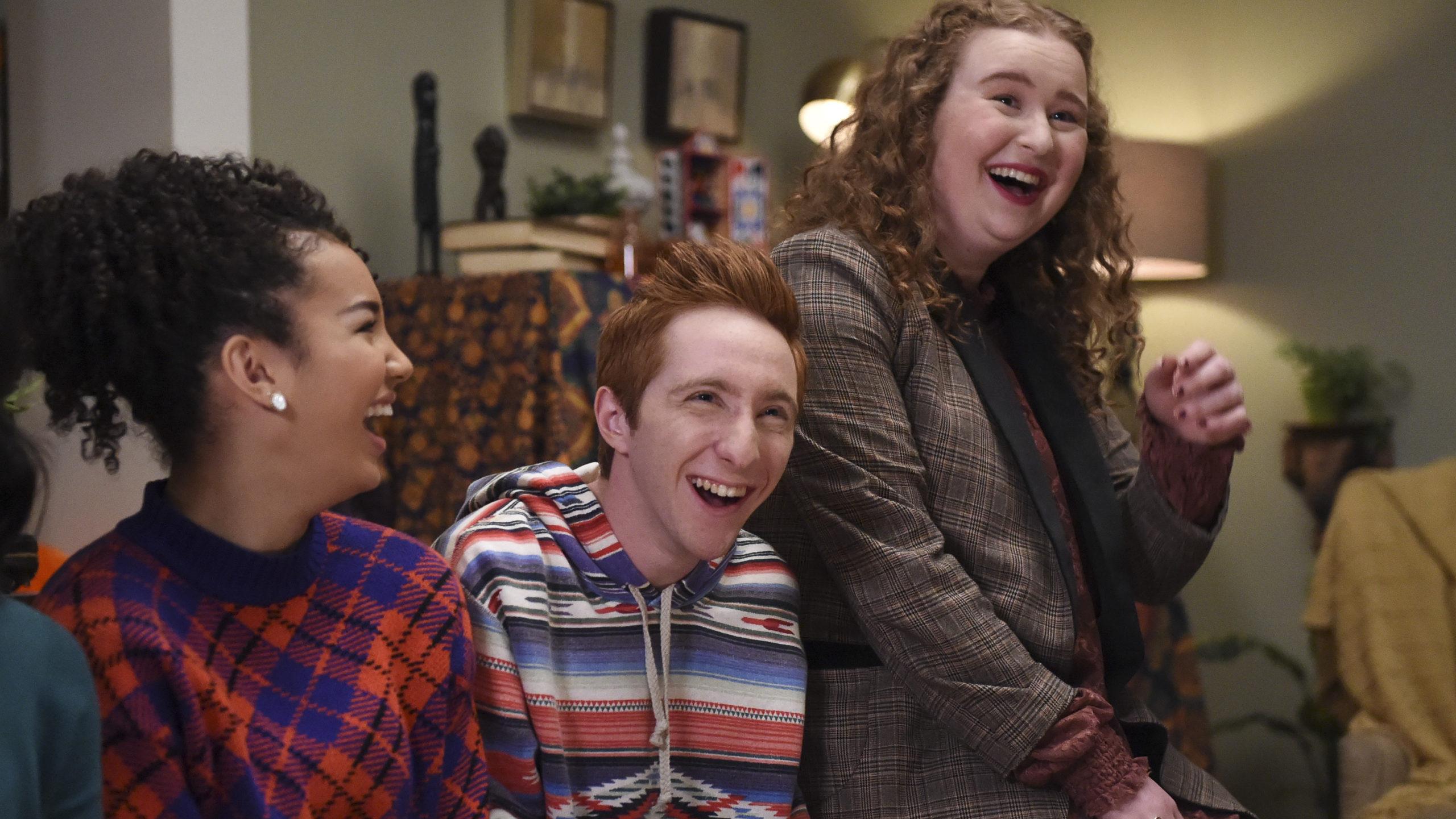 Cena da série High School Musical: The Musical: The Series. Vemos 3 personagens sentados no sofá e rindo. À esquerda está Gina, uma jovem negra e de cabelo enrolado, ela veste um suéter azul e laranja. Ao meio está Big Red, um jovem branco e ruivo de topete, ele usa uma jaqueta listrada branca azul e laranja. Na ponta vemos Ashlyn, uma jovem branca, de cabelos encaracolados e gorda. Ela veste uma jaqueta escura e tem cabelos ruivos.