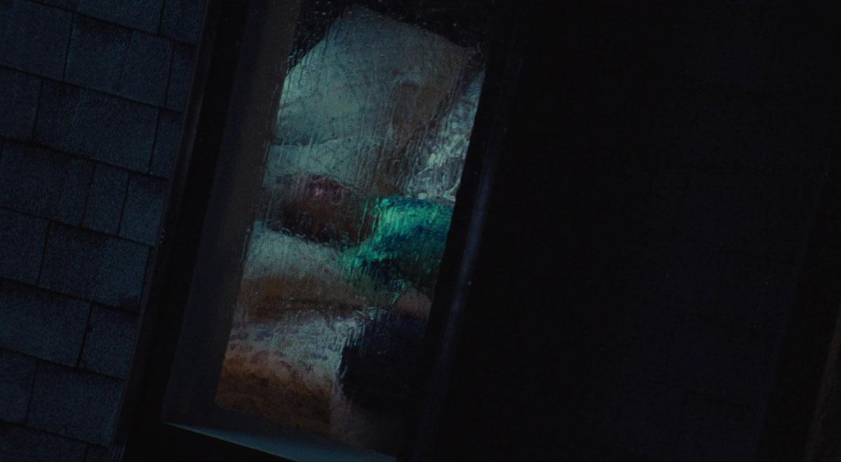 Cena do episódio Part 2: Jules de Euphoria. A cena filma a janela da casa de Jules e o vidro está embaçado e desfocado por conta da chuva. Vemos apenas o contornos da garota, sua pele clara, cabelos brancos e blusa verde. Ela está deitada na cama, chorando e olhando para o teto.