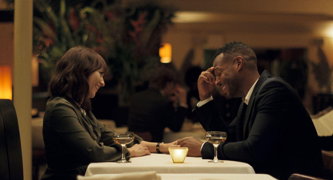 Cena de um jantar em restaurante do filme On the Rocks. Na ponta esquerda da mesa, Rashida, negra de pele clara sorri para o marido, eles estão de mãos dadas. Ele é Marlon, homem negro que usa terno e está com uma mão na testa, sorrindo