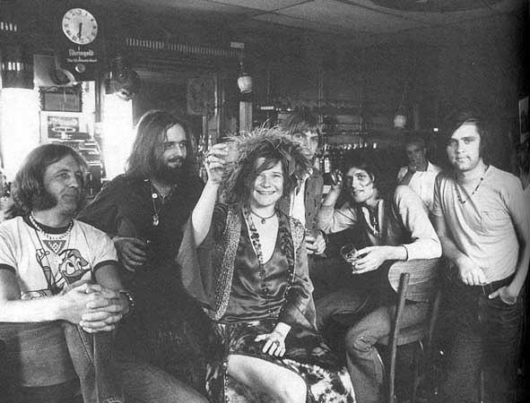 A imagem está em preto e branco. Nela, se encontram sete pessoas: seis homens e uma mulher. Estão todos sentados em cadeiras em um bar com copos na mão. A mulher está no centro da imagem, é branca e segura um copo no alto com um sorriso no rosto. Os homens estão ao seu redor e posam para a foto.