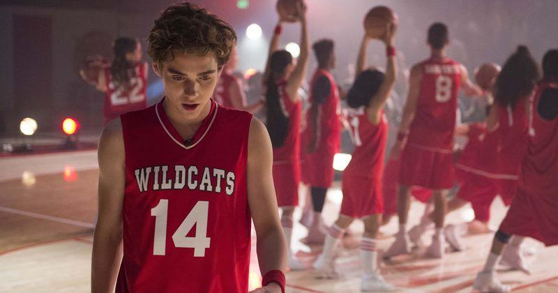 Cena da série High School Musical: The Musical: The Series. Ricky, um jovem branco, de pele clara e cabelo escuro encaracolado, está cabisbaixo e sem fôlego olhando para baixo. Ele usa o uniforme vermelho de basquete, uma regata com detalhes brancos na gola e escrito Wildcats 14 no peito. Ao fundo, vemos outras pessoas no mesmo uniforme reunidas, mas a imagem está desfocada.