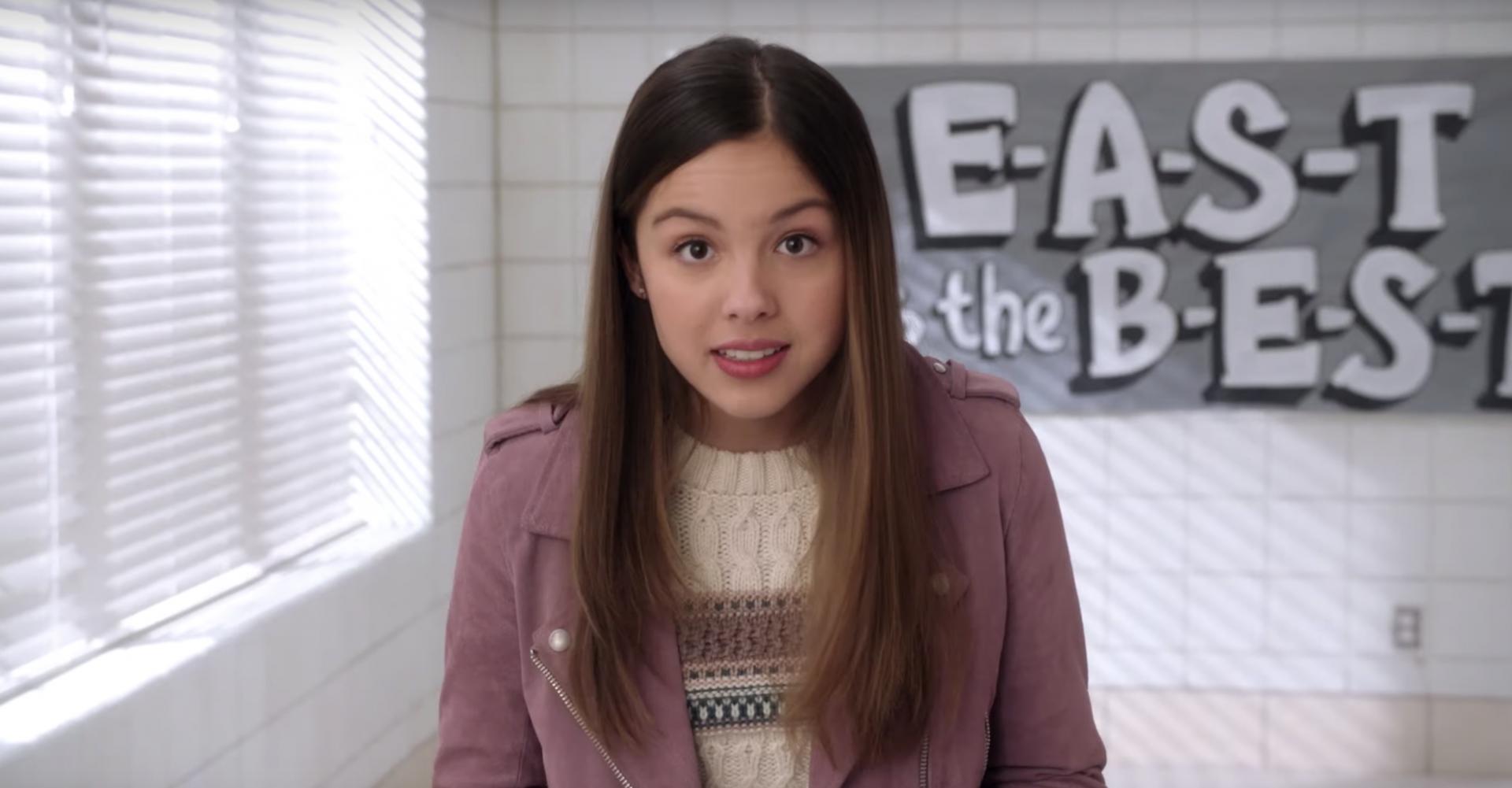 Cena da série High School Musical: The Musical: The Series. Nini é uma jovem de ascendência asiática, de pele clara e cabelos pretos. Ela está com uma expressão incrédula, olhando diretamente para a câmera. Ela veste uma jaqueta lilás e atrás dela vemos um cartaz desfocado.