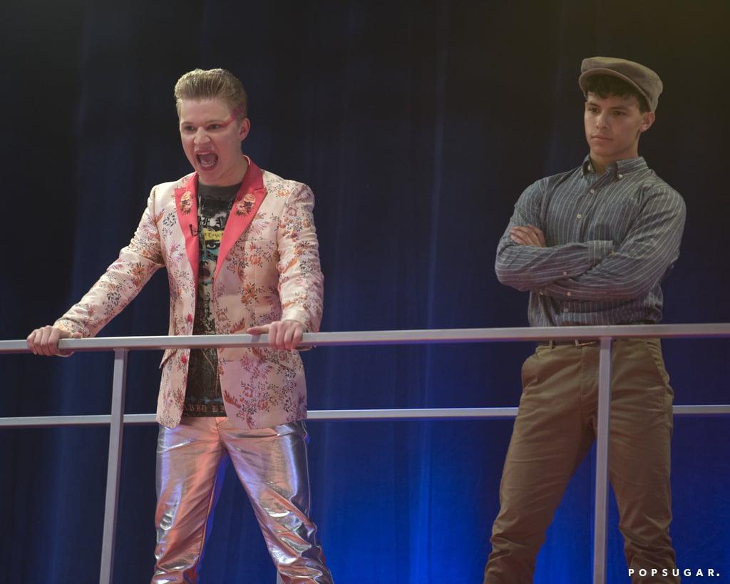 Cena da série High School Musical: The Musical: The Series. Vemos Seb, um jovem branco e loiro, vestindo jaqueta rosa, blusa preta e calça rosa, bravo e com as mão na grade do refeitório. Ele está com a boca aberta num sinal de descontentamento. Ao seu lado, mais atrás e de braços cruzados, está o intérprete de Ryan, de boina e camisa de botão azul.