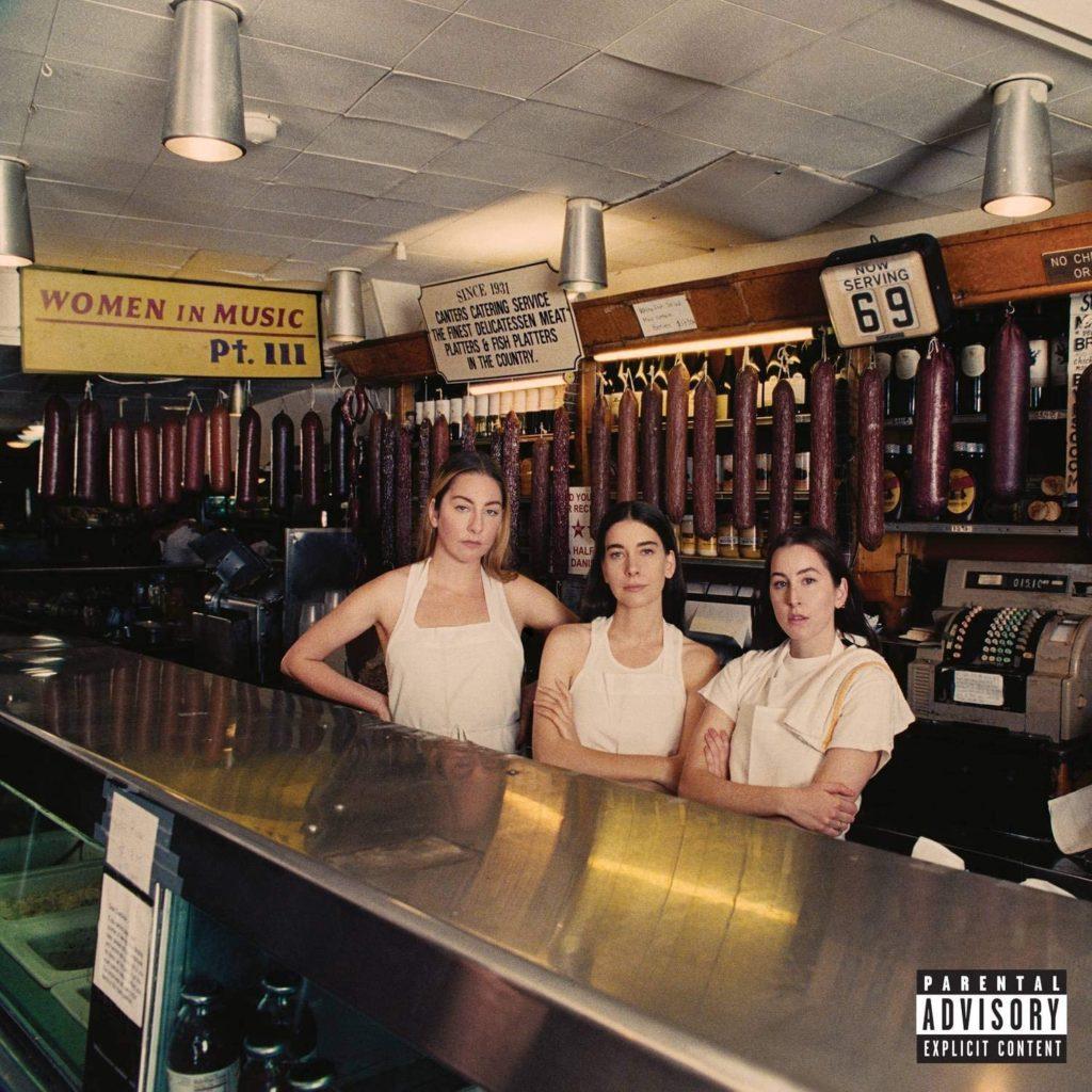 Capa do disco Women in Music Pt III, da banda HAIM. A capa é uma foto das três irmãs vestidas como bartenders e atrás de um balcão de rotisseria. As três usam camisetas brancas, tem a pele clara e o cabelo preso para trás. No canto superior esquerdo, vemos uma placa amarela com Women in Music escrito em vermelho Pt III em preto.