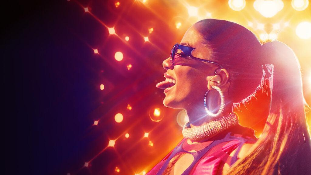 foto do pôster do documentário Anitta: Made In Honório, vemos a cantora Anitta, cantora branca, de perfil para a esquerda. Ela está com a língua para fora usando óculos escuros, brinco de argola brilhante e rabo de cavalo. Ao fundo há uma parede de luzes refletindo a artista.