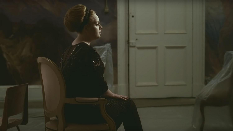 Imagem do clipe Rolling In The Deep. Mostra Adele sentada de perfil em uma cadeira grande. Ela tem os cabelos loiros presos em um coque e usa um vestido de manga três quartos e meia calça, ambos pretos. Ao fundo há uma grande porta branca.