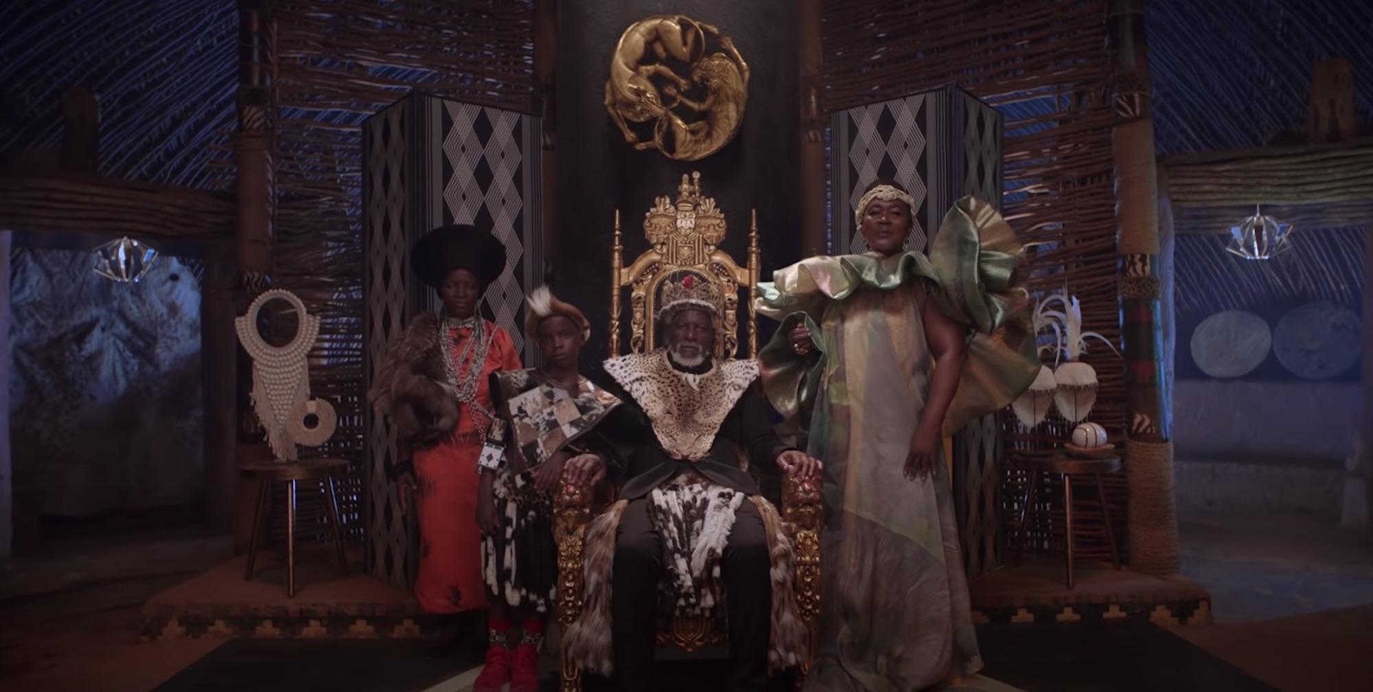 A imagem é uma foto de uma das cenas de Black Is King. Nela, há um homem negro, com barba branca, sentado em um trono. Ele está com uma coroa em sua cabeça e veste roupas de realeza que remetem à cultura africana. Ao seu lado direito, há um menino negro, e, ao lado esquerdo, há uma mulher negra. Ambos vestem roupas de realeza. Mais ao fundo, atrás do menino, há uma mulher negra com trajes da cultura africana.