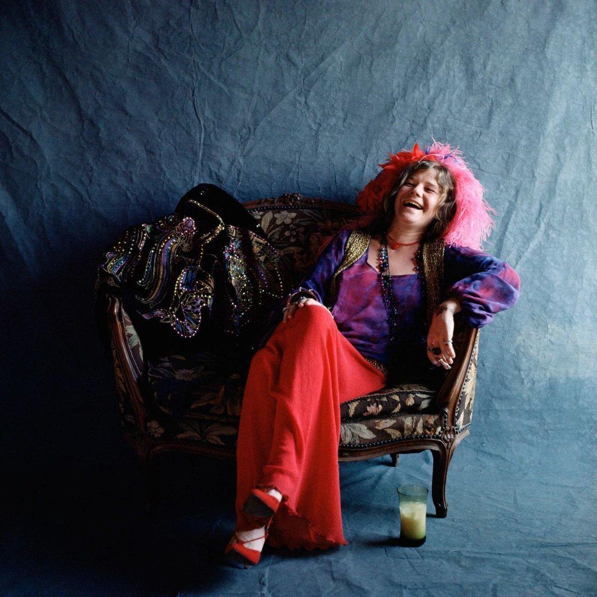Janis Joplin, uma mulher branca em torno dos seus 27 anos, está sentada em uma poltrona estampada. Ela está com as pernas cruzadas, o braço apoiado no encosto e dá uma gargalhada. Ela usa uma calça solta e vermelha, sapatos de bico fino vermelhos, uma blusa roxa de mangas compridas e plumas vermelhas no cabelo. O fundo é azul e há um copo com um líquido amarelado no chão.