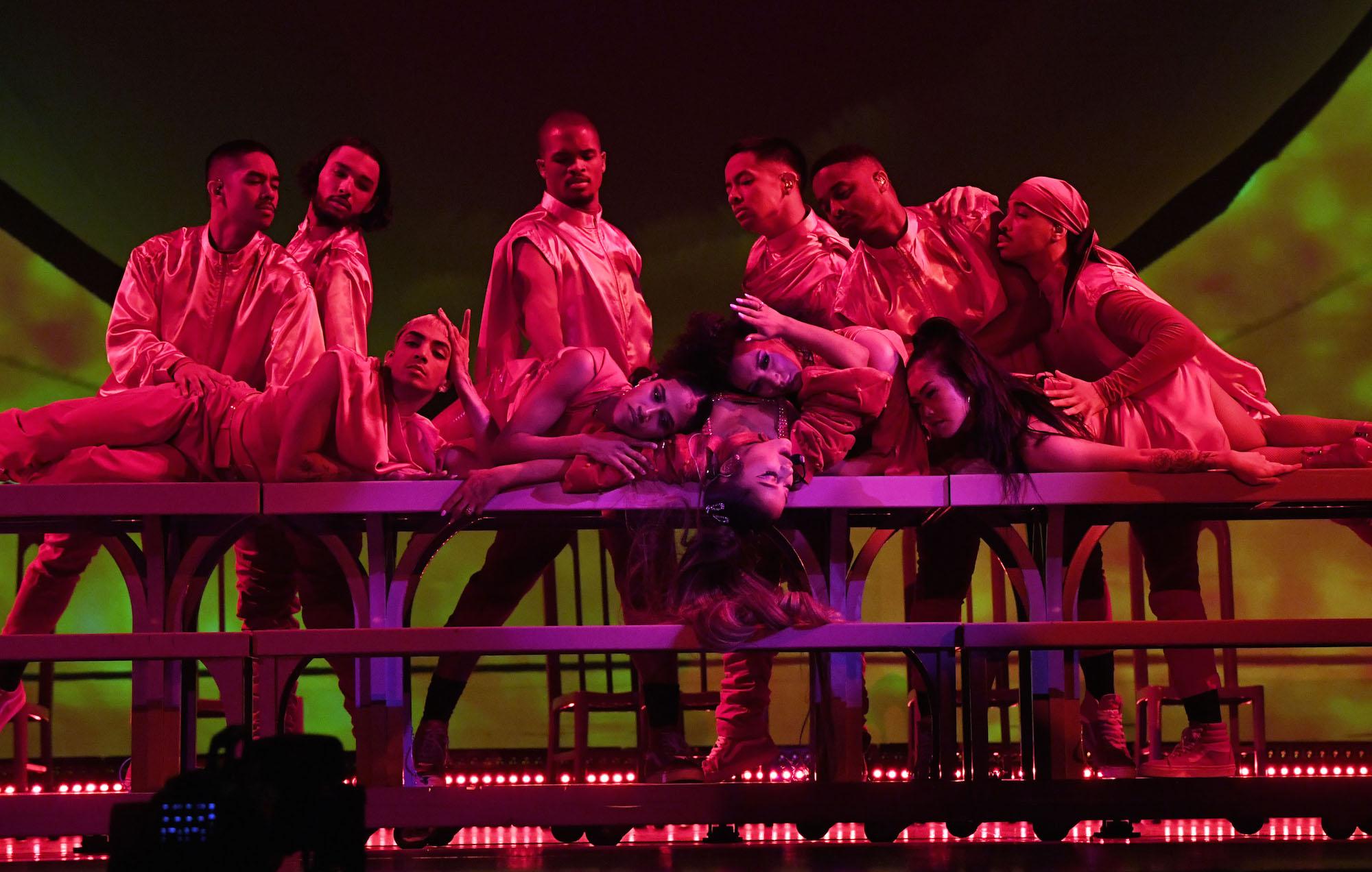 A foto mostra Ariana Grande deitada de cabeça para baixo em uma mesa longa. Ela está no centro, de olhos fechados. Seus cabelos castanhos são longos, na altura da cintura, e estão presos em um rabo de cavalo que cai sobre a mesa. Dez dançarinos se posicionam ao seu redor, sobre a mesa.