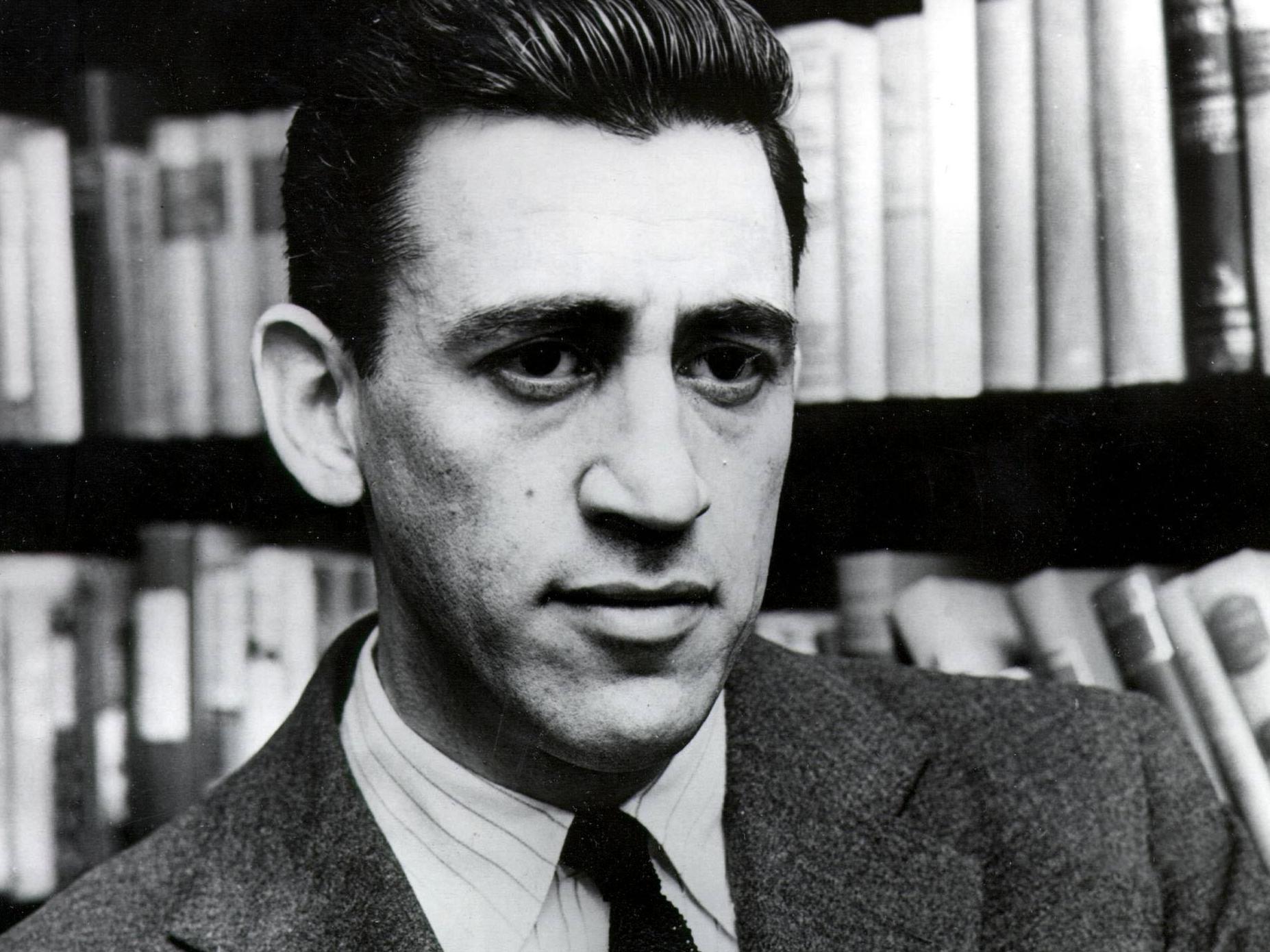 A imagem é uma fotografia em preto e branco do autor J.D. Salinger. Salinger era um homem branco de cabelos curtos lisos, formando um pequeno topete. Ele está vestindo um terno com uma camisa e gravata. Atrás dele, é possível ver uma estante de livros.