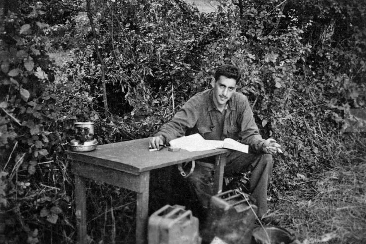 A imagem é uma fotografia em preto e branco do autor J. D. Salinger. Na imagem, o autor está sentado ao lado de uma mesa, no que aparenta ser um jardim. Salinger era um homem branco de cabelos curtos lisos e bigode. Ele está vestindo uma camisa de mangas compridas e uma calça larga. Seu braço direito está apoiado em cima da mesa, segurando o que aparenta ser um lápis, ao lado de um caderno. E o seu braço esquerdo está apoiado em sua perna. O escritor está olhando diretamente para a câmera.