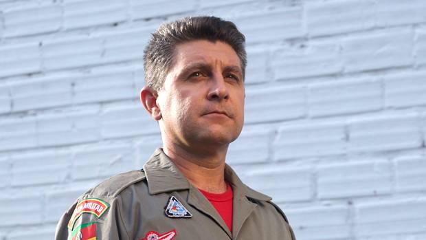 A imagem mostra o bombeiro Robson Muller que trabalho no resgate na tragédia da Boate Kiss. Robson é um homem adulto e com cabelo grisalho. Ele veste a farda de bombeiro na cor cinza com vários emblemas coloridos e uma camiseta vermelha por baixo. A parede no fundo, é azul.
