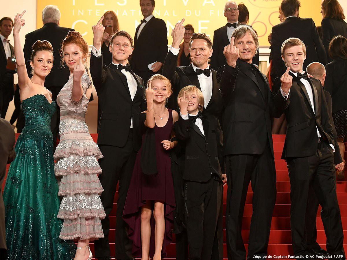 O elenco principal do filme está sobre o tapete vermelho do evento SAG Awards. Vestem roupas de gala e posam para foto com as mãos levantadas e o dedo do meio a mostra em forma de protesto anti-Trump.