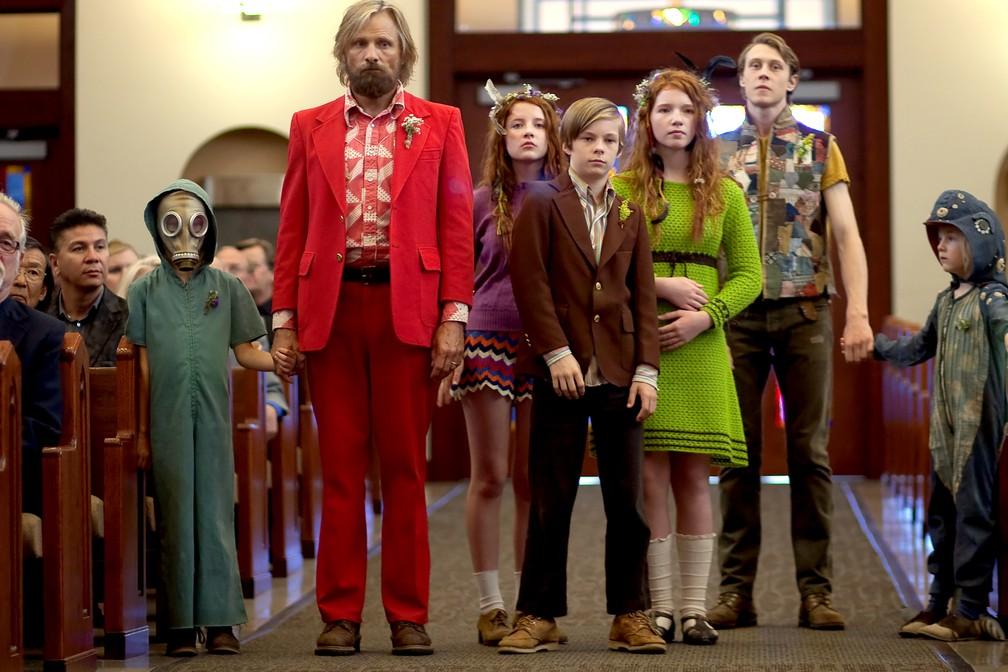 Cena do filme Capitão Fantástico, onde a família formada por três crianças, três adolescentes e um adulto, todos brancos com cabelos loiros e ruivos, está em pé dentro de uma igreja com detalhes marrons. As expressões são sérias e eles usam roupas coloridas num estilo hippie.