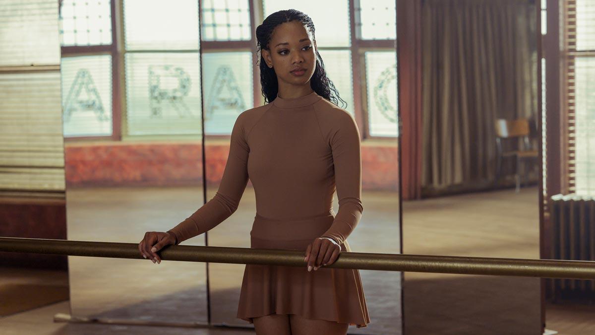A imagem é de uma cena da série O Preço da Perfeição. A imagem é de um estúdio de balé, com vários espelhos e barras. Há grandes vidrais também. Na imagem há uma mulher apoiada na barra olhando para o espelho. Essa mulher é a atriz Kylie Jefferson, ela é adulta, negra e veste uma roupa de balé marrom clara.