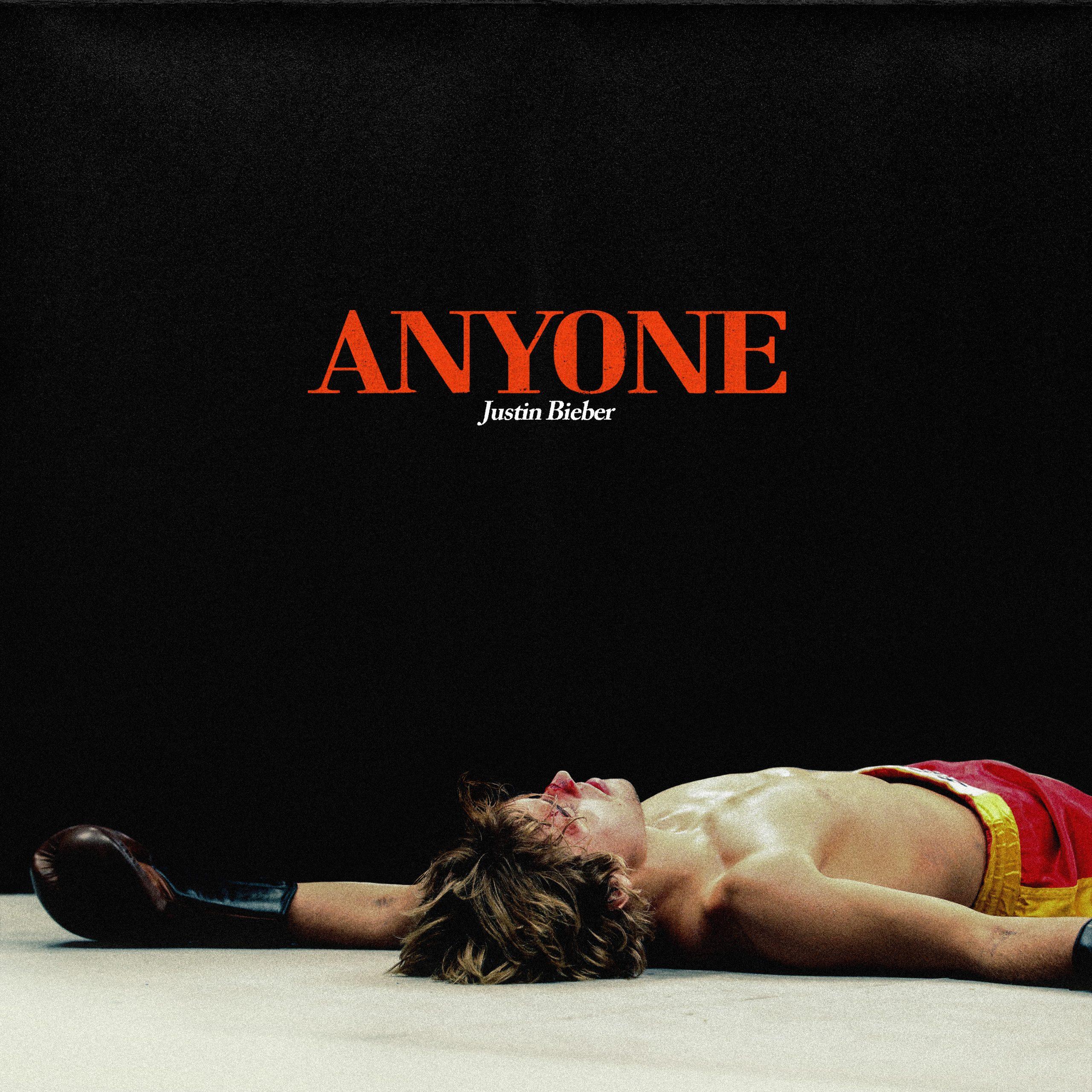 Capa do single Anyone. Justin Bieber, um homem branco e loiro, sem tatuagens, está deitado em um ringue de boxe com luvas marrons e um calção vermelho de faixa amarela. O fundo da imagem é preto, com letras laranjas escrito Anyone.