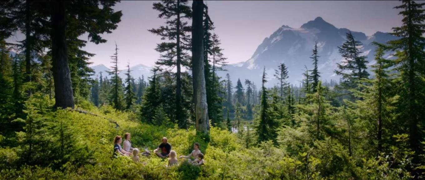 Cena do filme Capitão Fantástico, onde os 7 atores, brancos com cabelos ruivos e loiros, estão sentados em roda com as mãos sobre os joelhos. O grupo se encontra em meio a uma pequena clareira na floresta de pinheiros, as plantas são verde claro e há montanhas ao fundo.