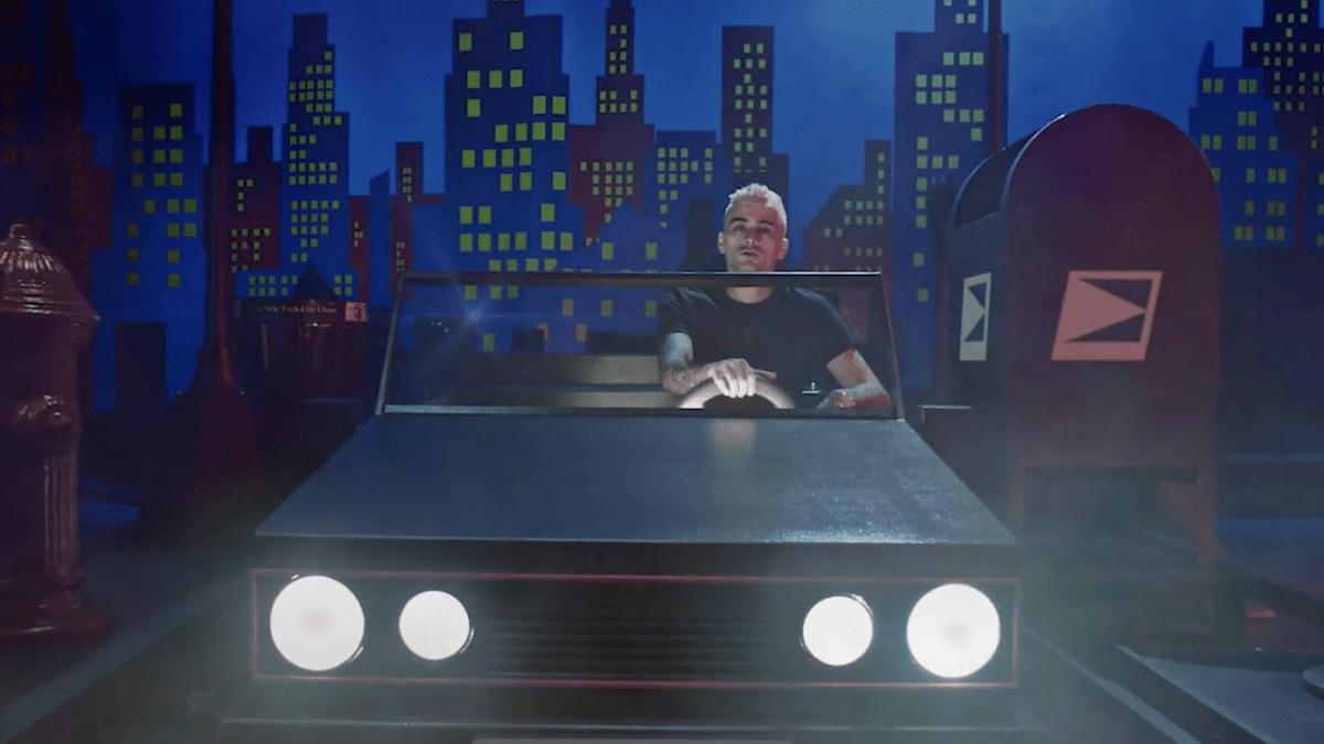 Imagem do clipe Vibez. Ela mostra Zayn, homem de cabelos platinados, dirigindo um carro pequeno com os faróis acesos. Ao fundo vemos um painel com o desenho de uma cidade. Ao seu lado direito há uma caixa de correio e ao esquerdo um hidrante.