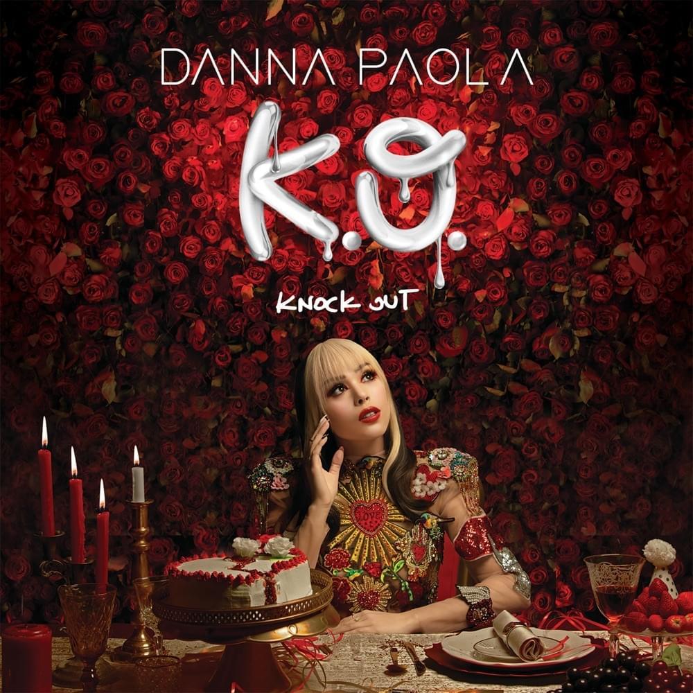 """Foto da capa do álbum Knock Out. Na parte superior, pode-se ler """"Danna Paola"""" em letras maiúsculas e brancas. Embaixo, """"K.O."""" em letras maiúsculas brancas grafitadas e seguido de """"Knock Out"""" também em letras maiúsculas e brancas. Fotografia quadrada com fundo de botões de rosas vermelhas com contraste mais escuro. Danna Paola se encontra no centro, com o cabelo loiro na franja e algumas mechas frontais e morena na parte de trás. Ela possui maquiagem vermelha nos olhos e na boca. Ela veste uma fantasia de ombreiras com elementos que remetem ao México. Ela está sentada em frente a uma mesa de banquete. A mão direita está erguida na altura das maçãs do rosto com os dedos elevados. Sua mão esquerda está apoiada sobre a mesa. No canto inferior esquerdo, há um pote vermelho, um castiçal com três velas vermelhas acesas, um copo em bronze e outro castiçal bronze com uma vela pequena acesa e branca. Ao lado, há um bolo branco em forma de coração partido com um glacê vermelho fazendo o contorno. Sob ele, há três rosas, sendo duas brancas na frente e uma vermelha atrás. Ele está em cima de um suporte específico para bolos. Embaixo desse suporte há um copo pequeno de cristal. Em frente a mão esquerda de Danna, há uma colher e uma faca em bronze. No canto inferior direito, há um prato branco grande com outro prato branco pequeno e um guardanapo bege envolvido numa fita dourada. Há uma taça de cristal meio cheia com vinho, um suporte branco com morango e uma rosa branca ao topo como decoração. Embaixo desse suporte, há uvas."""