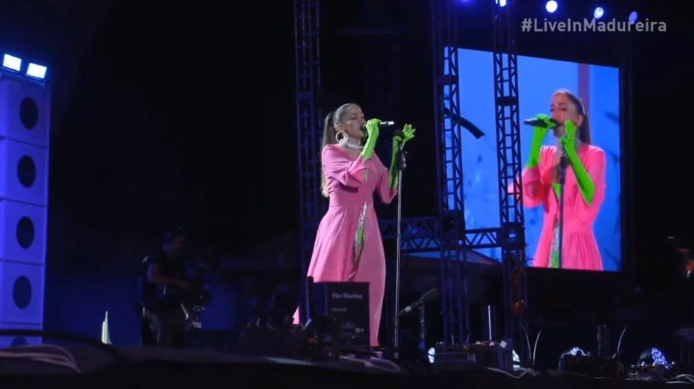 cena do show de Anitta no Parque de Madureira. Ela é branca, está no palco vestindo um robe rosa pink e usa luvas verde-limão que se estendem até seus cotovelos. Na mão direita ela segura o microfone enquanto canta para a plateia, e com a mão esquerda segura o pedestal do microfone.
